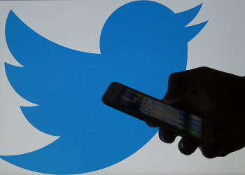 """ANKARA, TURKEY - MARCH 16: A picture shows a man holding a cellphone in front of a twitter logo in Ankara, Turkey on March 16, 2017. """"Twitter"""" suspended 636,248 accounts for pro-terrorism and violence contents since the mid 2015 until the end of 2016. (Photo by Gokhan Balci/Anadolu Agency/Getty Images)"""