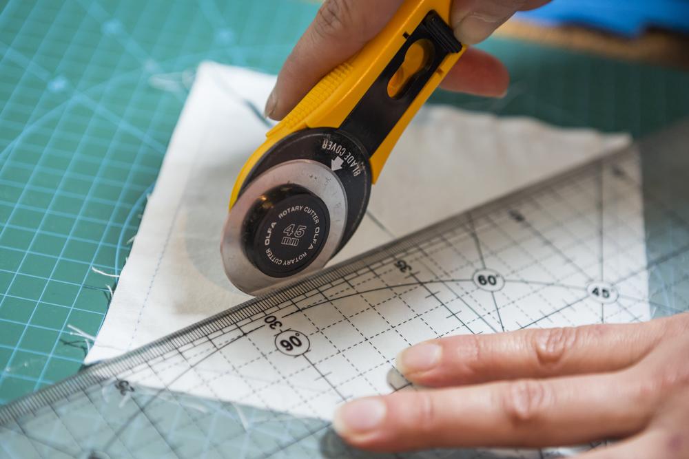 Diseñador usando un cutter para cortar tela