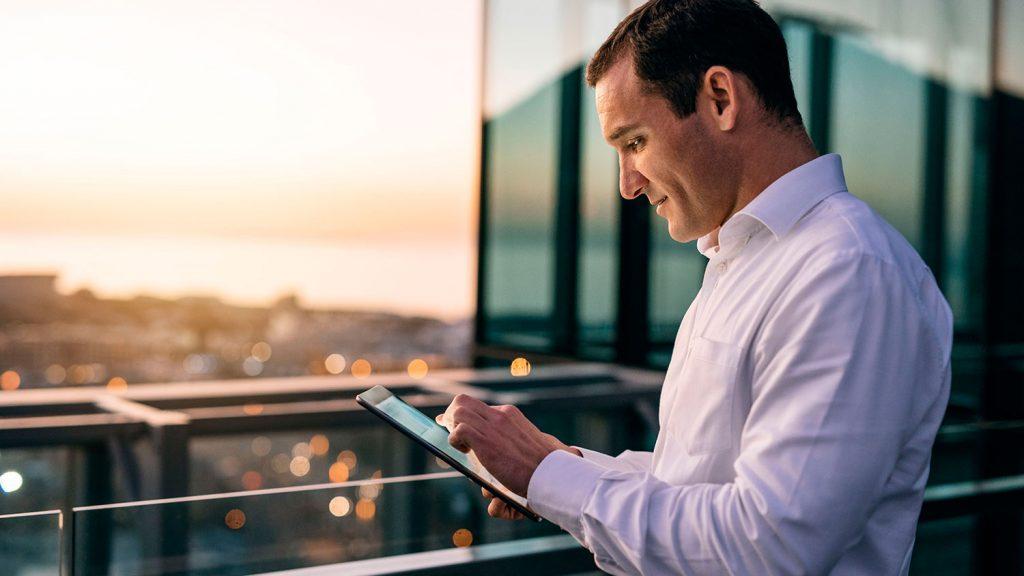 Hombre busca en su tablet sobre VP sales y VP operaciones