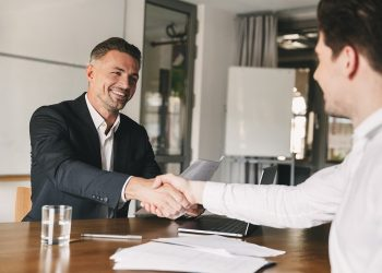 Business, career and placement concept - joyful handsome businessman 30s smiling and shaking hands with male candidate who was recruited during interview in office
